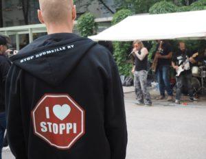 Stop Huumeille ry:n pihassa on päihteetön tapahtuma menossa, jossa on bändi esiintymässä. Henkilö katsoo bändiä Stop Huumeille ry:n hupparissa.